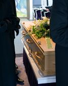 stock photo of mortuary  - A coffin with a flower arrangement and bearers at a mortuary - JPG