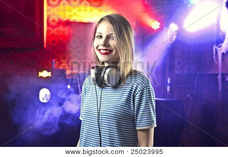 Smiling beautiful female dj in a disco