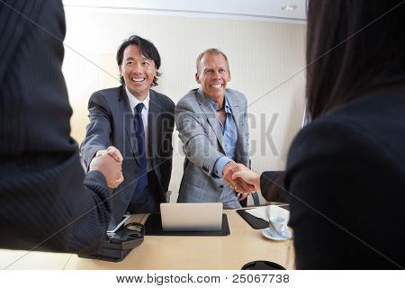 Smiling business people shaking hands in office