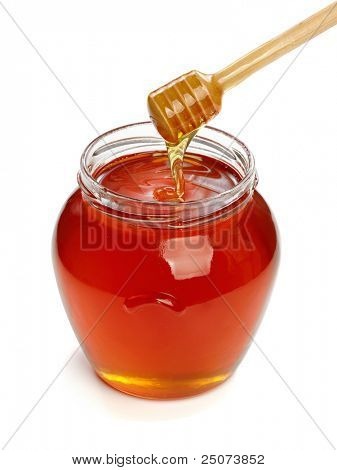 Wooden dipper with jar of honey, isolated on the white background, clipping path included.