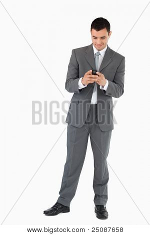 Young businessman reading textmessage against a white background