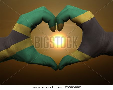 Heart And Love Gesture By Hands Colored In Jamaica Flag During Beautiful Sunrise