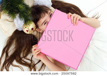 Pretty Little Girl Lying Under A Christmas Tree With Present