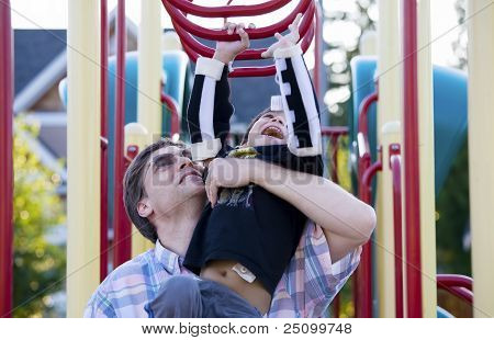 Active Disabled Five Year Old Boy Playing On The  Monkey Bars With His Father