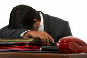 picture of deprivation  - a man sleeping behind his office desk - JPG