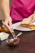 Detail Of Female Hands Taking Some Jam With A Kitchen Knife, Making Jam And Butter Sandwich For Brea poster