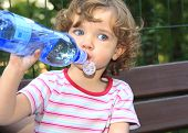 picture of drinking water  - The little girl is drinking water from the plastic bottle - JPG