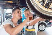 Two dedicated auto mechanics tuning a car through the modification of the rims, while working togeth poster