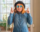 Stylish redhead woman wearing bowler hat and sunglasses smiling crossing fingers with hope and eyes  poster