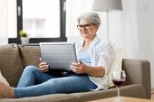 technology, old age and people concept - happy senior woman in glasses with laptop computer and glas poster