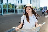 Young Relaxed Traveler Tourist Woman In Hat, Light Clothes Hold Paper Map At International Airport.  poster