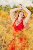Beautiful Auburn Haired woman outdoors in nature poster