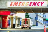 Ambulance Car In Front Of Emergency Entrance. A Modern Ambulance Car Parked Near The Emergency Entra poster