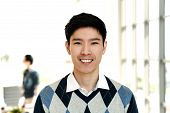 Portrait Of Young Attractive Asian Creative Man Smiling And Looking At Camera In Modern Office Feeli poster