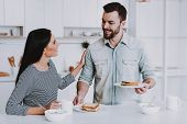 Young Couple Have Breakfast In Modern Kitchen. White Coffee Cup. Breakfast At Morning. Happy Wife An poster