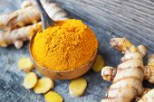 Turmeric Powder And Fresh Turmeric In Wooden Bowls On Old Wooden Table. Herbs poster