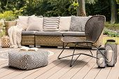 Patterned Pouf And Rattan Chair On Wooden Patio With Pillows On Sofa And Lanterns. Real Photo poster