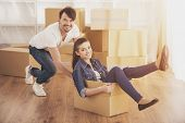 Happy Couple Is Having Fun. People With Boxes. Family In New Flat. European Man And Woman. Fooling A poster