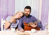 Couple In Love Holds Cups Of Coffee At Table. Woman And Man With Dreamy Faces Read Books Having An A poster