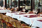 Постер, плакат: Типичный тротуаре ресторан сцена в Париже с столы и стулья для еды