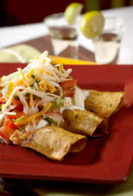 stock photo of flauta  - Flautas on a red plate with cheese and pico de gallo on top - JPG