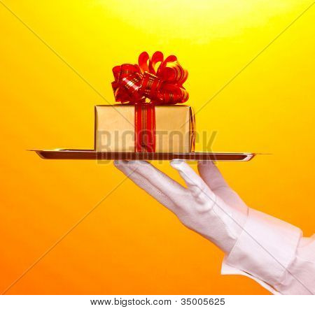 Hand in glove holding silver tray with giftbox on yellow background