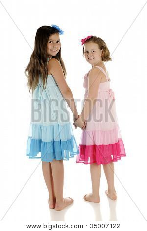Two elementary best friends, holding hands and looking back over their shoulders.  They wear identical undresses except one is blue, the other pink.  On a white background.