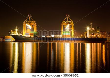 Container Cargo freight Industrial ship with working crane bridge unloading and loading goods in Bangkok shipyard Terminal at night for Logistic Import Export background