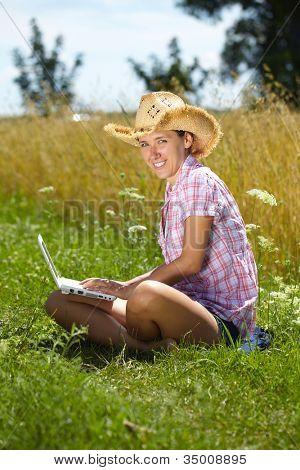 Happy attractive female work on her laptop, summer outdoor shoot