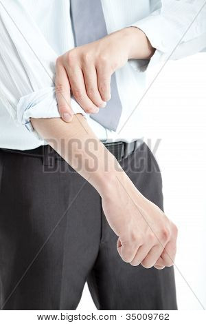 Businessman rolling his sleeves up