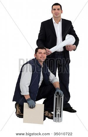 Portrait of an engineer and a workman holding a tile and a ceramic tile cutter