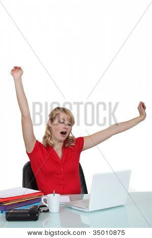 Woman yawning at a desk