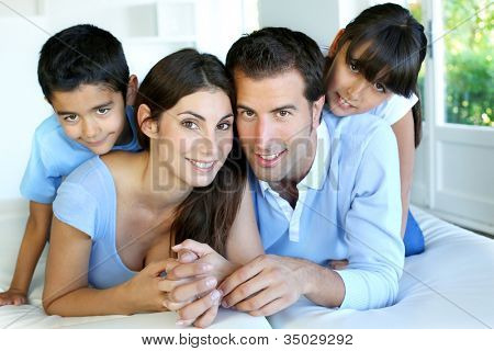Portrait of happy family laying down bed