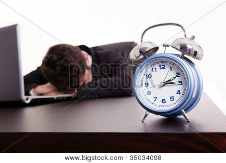 Exhausted young business man sleeping next to his laptop at the desk, isolated on white