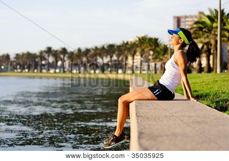 healthy woman relaxing after exercise sitting near the water in an urban park space