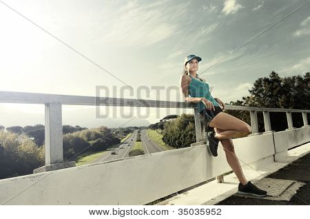 portrait of an athlete resting after running workout outdoors on a bridge. healthy fitness woman
