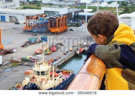 Boy wearing in plaid look at loaders, ship and buildings in port