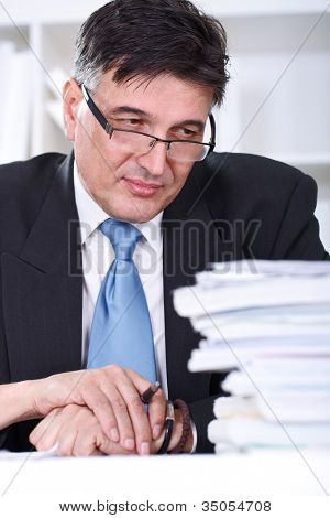 Overworked senior businessman looking in stack of document