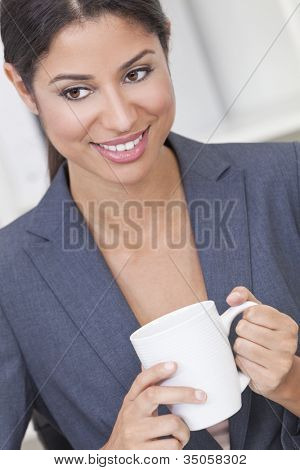 Beautiful young Latina Hispanic woman or business woman smiling, relaxing and drinking a cup of tea or coffee in her office