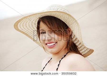 Smiling woman in straw hat, sitting on beach. Happy pretty girl in summer time.