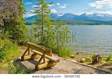 Picnic bench (chair) on the beach of the mountain lake in Canada.