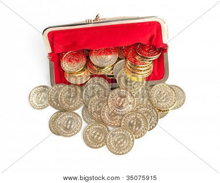 Scattered silver and gold coins are in red purse, isolated on white background. A great number of coins symbolize wealth, richness, income and profit. Close up shot.