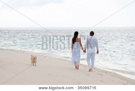 Picture of romantic young couple having a walking on the sea shore with dog