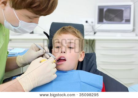 Dentist in mask looks at teeth of little boy in dental clinic. Focus on patient.