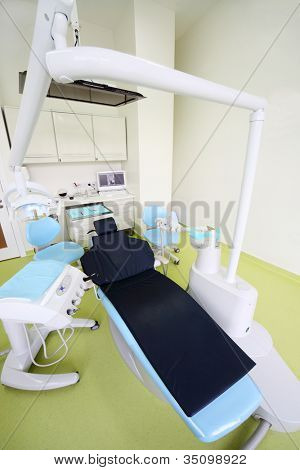 Empty light dental clinic. Chair for patient and large drill for dentist.