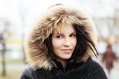 Young woman wearing furry hood during cold day. poster