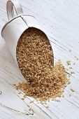 picture of shabby chic  - Scoop of brown rice over rustic timber background - JPG