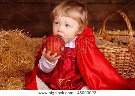 Little Girl Is Sitting On Pile Of Straw Eating Apple. Little Red Riding Hood