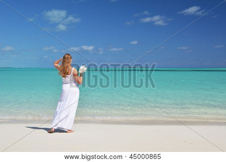 Girl with a shell in her hand on the beach of Exuma, Bahamas