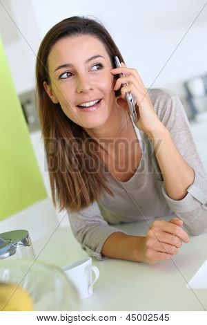 Woman in kitchen talking on the phone